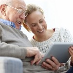 Carer helping elderly gentleman do his online food shopping